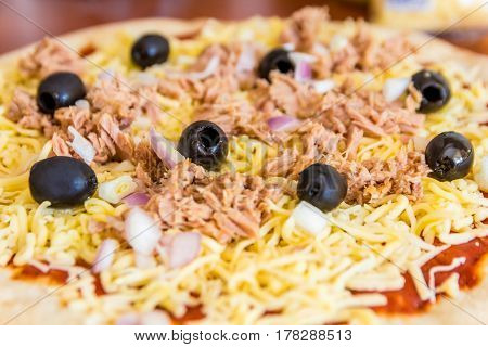 pizza topped with onions, olives, cheese an tuna