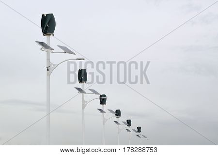 Wind power turbines and solar panels in a power generation plant. Cloudy sky and empty copy space for Editor's content.
