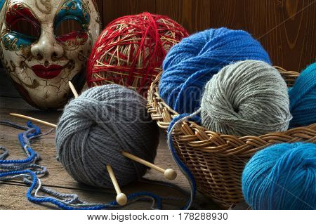 Knitting needles wool balls and carnival mask on a wooden table