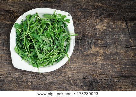 Fresh arugula in a plate on rustic wooden background with place for text. Healthy organic diet vegan food concept. Green meal. Top view. Copy space.