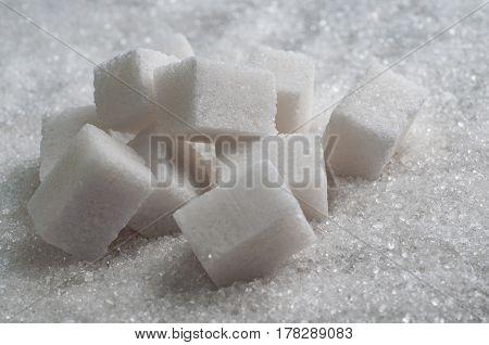 White cubes sugar on granulated sugar background.