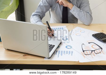 Businessman Analyzing Charts And Graphs With Modern Laptop Computer And Calculator.