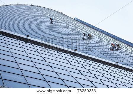 Window washers cleaning the windows of the modern high-rise building.
