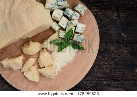 Grated Parmesan and sliced Blue cheese with basil on wooden chopping board on old wooden background. Tasty appetizers. Top view.