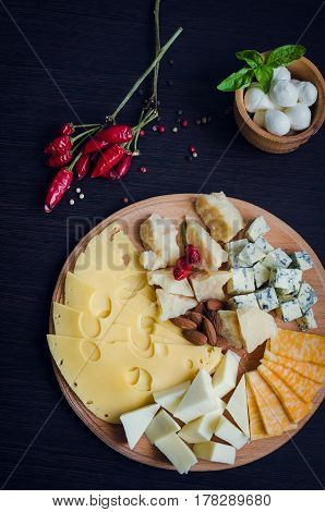 Cheese plate: Parmesan cheddar gouda mozzarella and other with chili pepper and almonds on wooden board. Tasty appetizers. Top view.