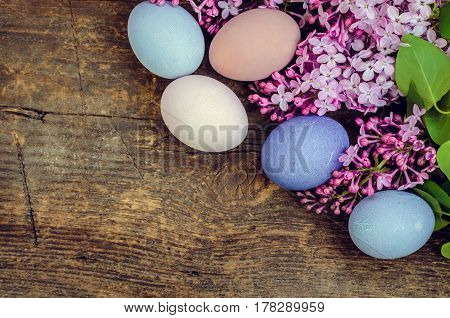 Easter background with handmade painted purple eggs and lilac on a wooden vintage board with place for text. Top view. Copy space.
