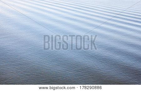 Water surface with ripples and the wake of a boat.