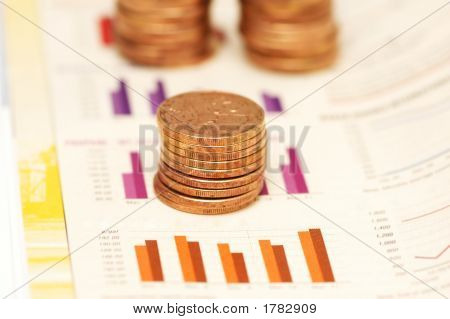 Stack Of Coins Over Bar Charts With  Shallow Depth Of Field