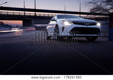 Engels, Russia - March 15, 2017: White car Toyota Camry XV50 is parked near bridge at dusk