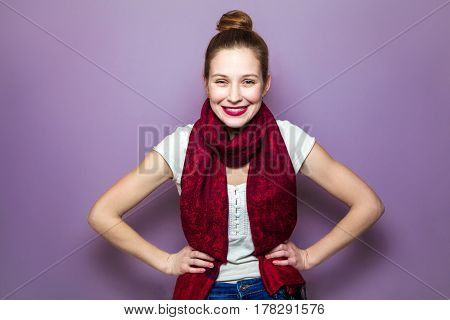 Funny woman with white t-shirt and red scarf and hands on waist on purple background. Cheerful female model joyful. Positive human emotion facial expression body language.
