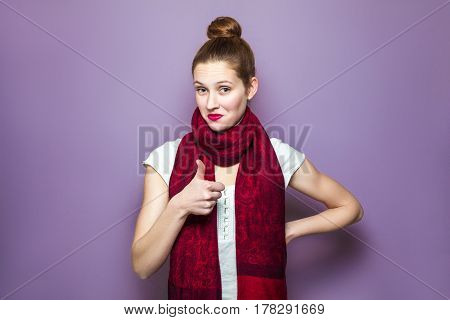 Thumbs up young emotional girl with collected hair freckles and red scarf looking excited with thumbs up on purple background showing her thumb finger with happy funny face looking at camera.