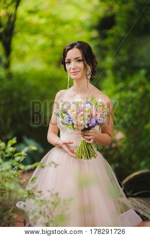 Half-length portrait of a beautiful bride in park. Cute lady with a bouquet in pink wedding dress outdoors. Grass trees and bushes in the background.