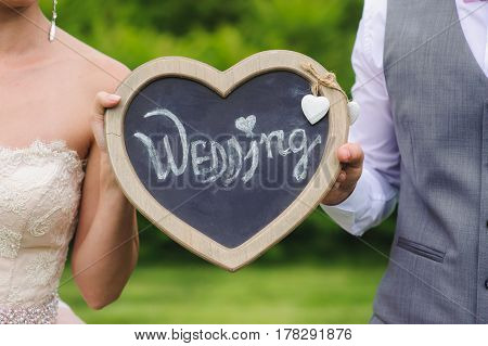 Romantic couple holding heart outdoors. The plate with the inscription closeup. Bride and groom holding wooden plate for inscription. Sign in the form of heart with words wedding.