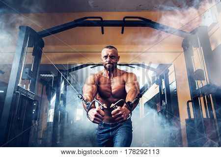 Bodybuilder Is Working On His Chest With Cable Crossover In Gym. Smoke on background