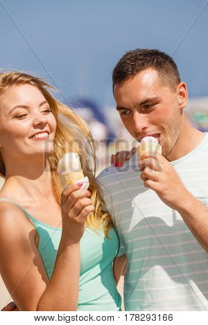 Relationship goals summer love concept. Man and woman being on date eating ice cream on beach and having fun.