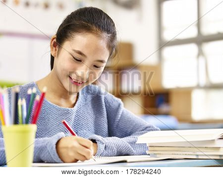 11 year-old asian schoolgirl doing homework happy and smiling.