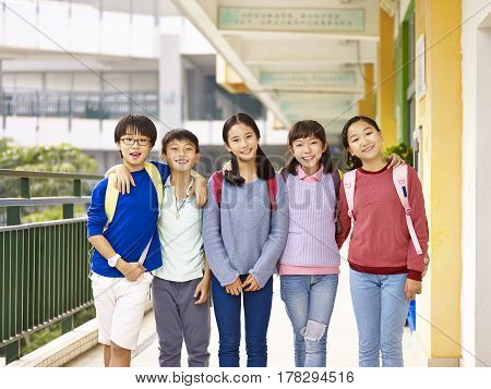 group of happy and smiling elementary schoolboys and schoolgirls standing in hallway of classroom building on campus.