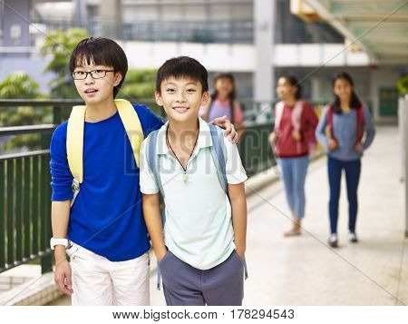asian primary school students walking in hallway of classroom building.