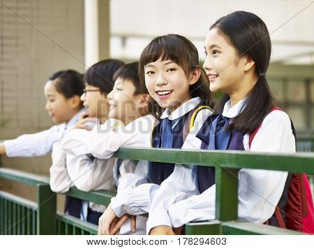 asian elementary school girl looking at camera smiling confidently.