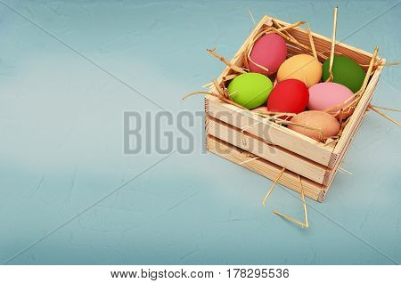 Bright colored easter eggs in a wooden box. Blue green background.
