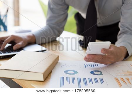 Businessman Analyzing Charts And Graphs With Smartphone And Computer.