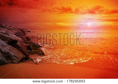 Some rocks in the beach at sunset. Red cloudy sky. Empty copy space for Editor's text.