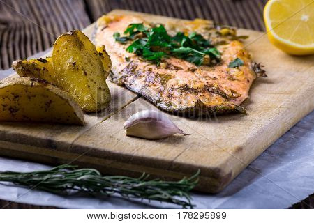 Trout steak with baked potateos garlic, rosemary and vagetables on wooden board.