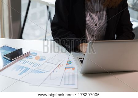 Business Woman Hand With Financial Charts And Laptop On The Table In Office