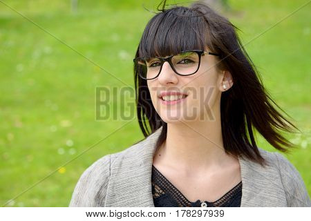 portrait of young smiling brunette girl outdoors