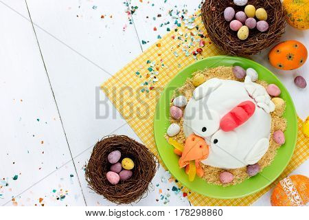 Easter sweets and treats: Easter eggs Easter chick fondant cake and candy mini eggs on white background top view