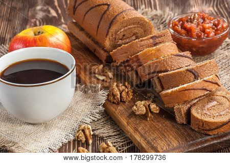 Tasty cake roll and cofee on old wooden table. Rustic style