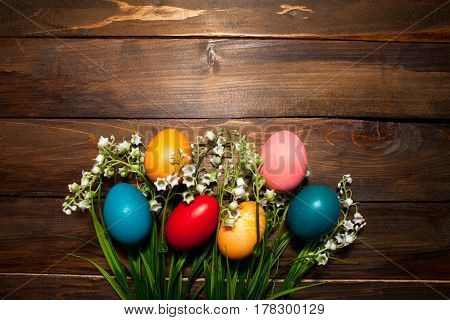 Multi-colored, Bright Easter Eggs With Green, Spring Lilies Of The Valley On Wooden Background