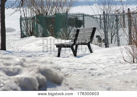 A vacant bench in a big park filled with deep snow