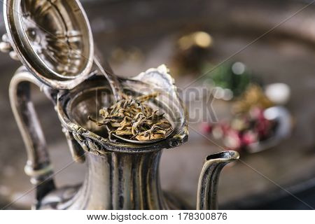 Dry green tea leaves in metal vintage spoon over old style open teapot, selective focus, horizontal composition. Healthy clean eating lifestyle concept