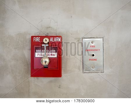 Push button switch fire alarm on mortar wall for alarm and security system with fire extinguisher port.