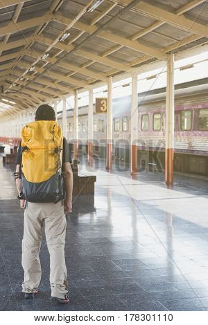 Young Man Walking On The Station Platform With Backpack On Train Station