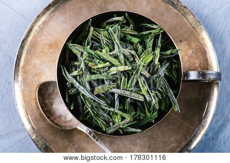 Dry green tea leaves in metal cup over wooden serving board, top view, selective focus, horizontal composition. Healthy clean eating lifestyle concept