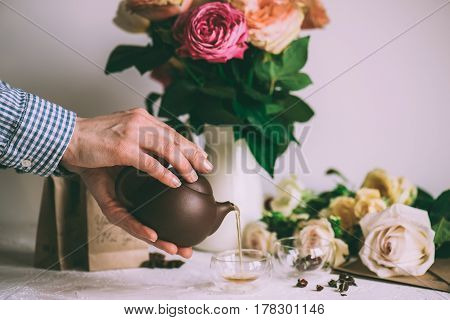 Human hands pouring Fresh herbal tea fron teapot to glass, colorful flowers at background, selective focus. Healthy lifestyle concept