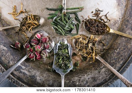 Variety of green and herbal teas in spoons on vintage metal tray over grey background, top view, close-up, horizontal composition. Healthy clean eating lifestyle concept