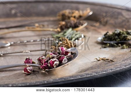 Variety of green and herbal teas in spoons on vintage metal tray, selective focus, close-up, horizontal composition. Healthy clean eating lifestyle concept