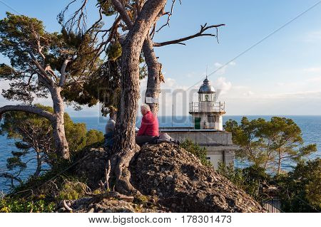PORTOFINO, ITALY - DECEMBER 2016: Old people are sitting on a stone near white lighthouse, located at coastline of Portofino town, Italy