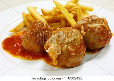 Meatballs with tomato sauce and french fried potato chips close up