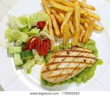 Grilled chicken breast on a bed of green pea puree and peas, served with a salad and french fried potato chips, top view