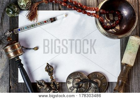 Tibetan musical instruments for meditation and alternative medicine in the middle of a clean white sheet of paper