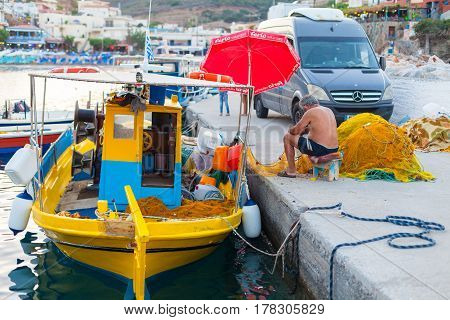 Bali Island Crete Greece - June 30 2016: Fisherman are repairing the fish net near fishing boat on the pier located in village Bali on Crete island in Greece.
