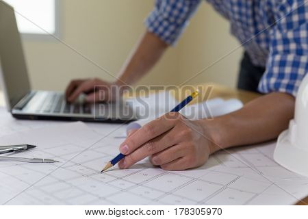 Architect Or Engineer Working With Blueprints And Laptop In Office, Construction Concept.