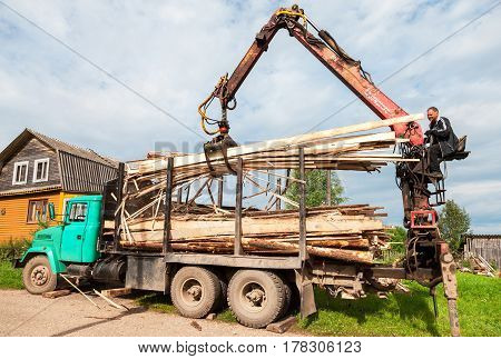 Novgorod region Russia - july 25 2016: Log hydraulic manipulator unloaded timber from the truck in summer day