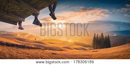 Hikers sit on a wooden flooring above the carpathian mountain valley and enjoy golden sunset.