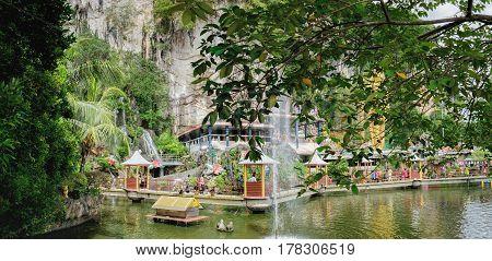 Batu Caves, Malaysia - February 7, 2016: Beautiful pond with gazebo for walking tourists at the entrance to the Batu Caves Malaysia