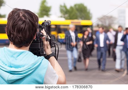Camera operator filming unrecognizable group of people